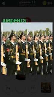 стоит шеренга военных с оружием в руках по стойке смирно