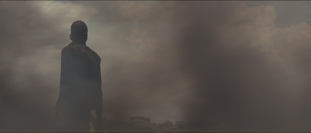 Elektroniikkajätteen kaatopaikalta Ghanasta otettu kuva, jossa kaatopaikalla työskentelevä mies lähes häviää paksuun harmaaseen savuun, joka syntyy jätteen polttamisesta.