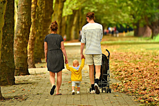 young family walking down path