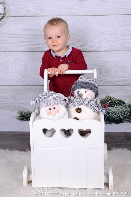 photo enfant qui pousse chariot blanc avec doudou de noel