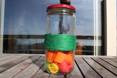 frasco com tiras de papel colorido