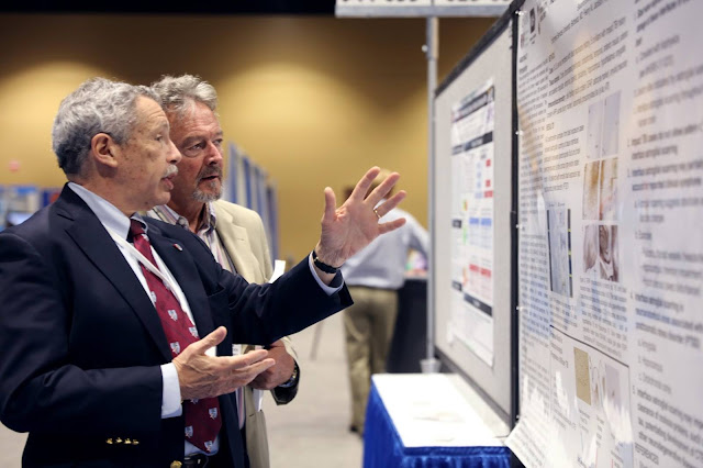 Two men examine a poster board.