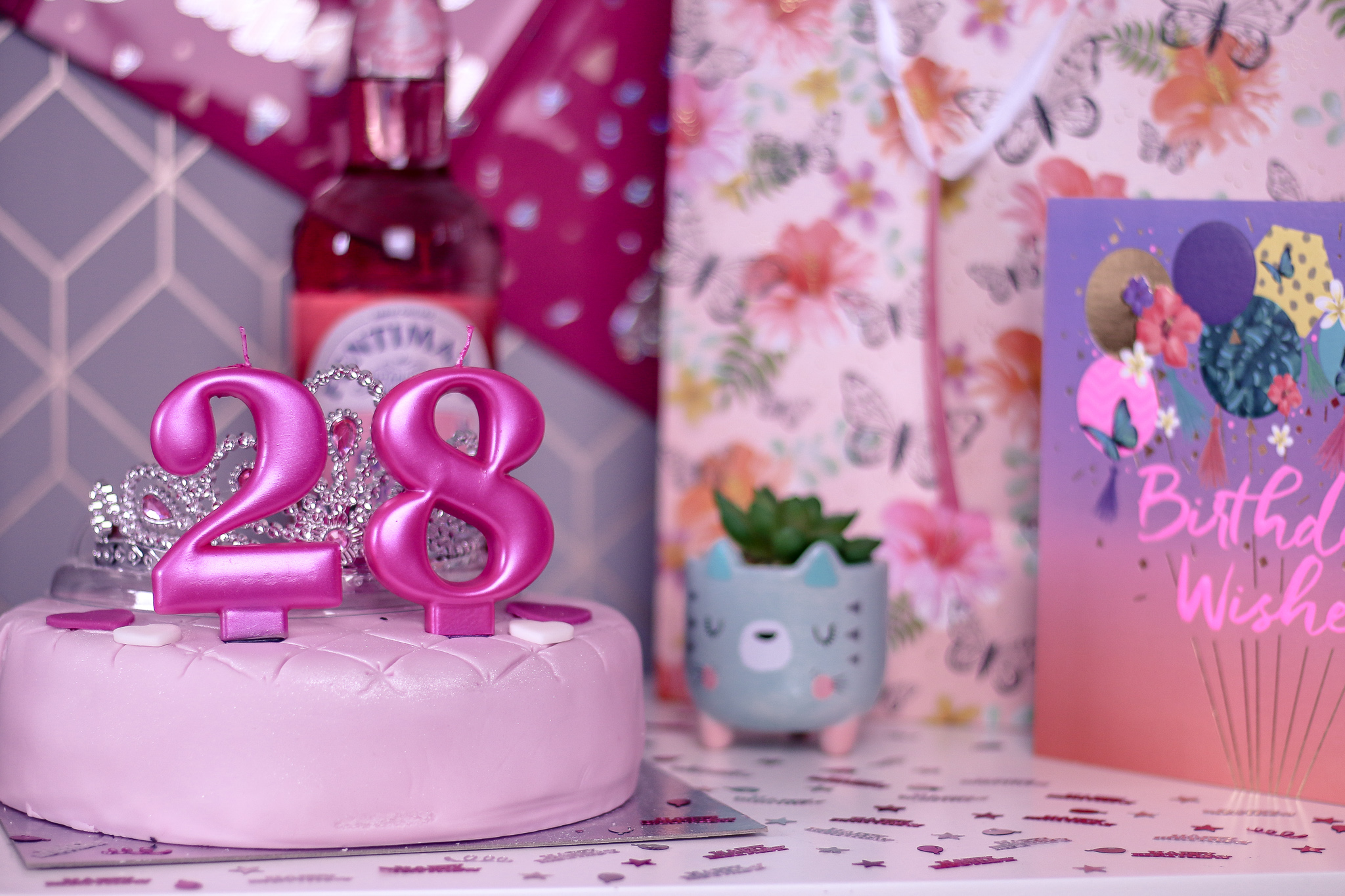 Close up photo of a pink cake with 2 and 8 candles on it