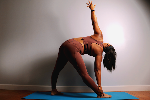 Black woman in yoga triangle pose wearing a tan prAna outfit and standing on a blue yoga mat