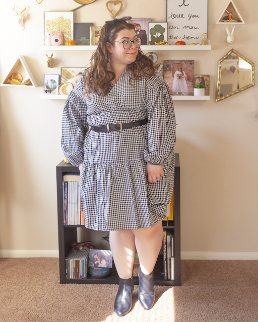 An outfit consisting of a black mesh ribbon tied in a bow on the head, a black on white gingham babydoll dress with bishop sleeves with tiers, belted at the waist and a black belt and black chelsea boots.