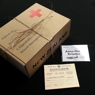 Cardboard box made to resemble a Red Cross box, next to a ration book and a name tag for NZAME convention 2016.