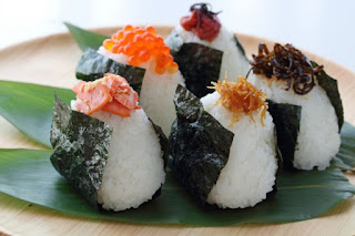 Five white triangle-shaped rice balls wrapped in black nori seaweed, each with a different ingredient on top.