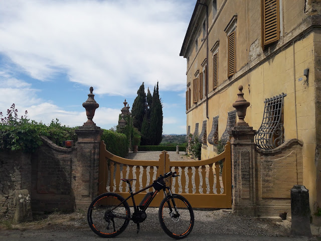 An e-bike in front of the gate of a Tuscan villa