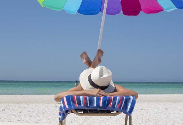 Someone laid on a sun lounger on the beach with a umbrella above them and the sea in the background.