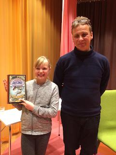 Molly Arnlund vann krumelurs tävling 2017 med temat rymden. Författaren Jakob Wigelus delade ut priset.