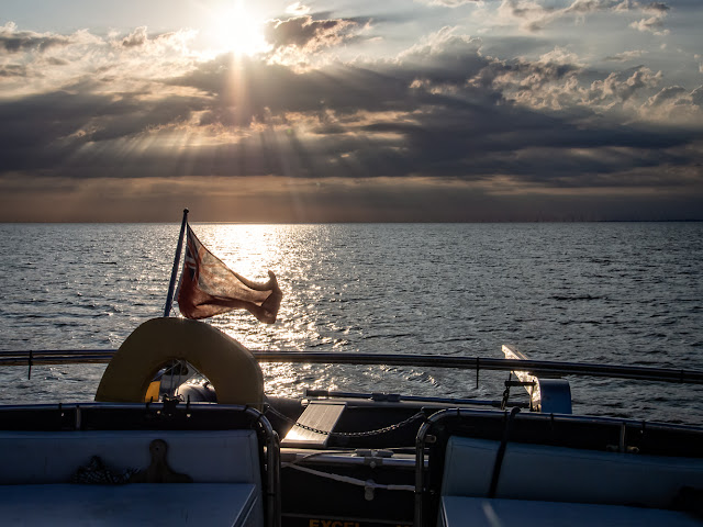 Photo of Sun breakimg through the heavy clouds over the Solway Firth as Ravensdale's flag blows in the wind