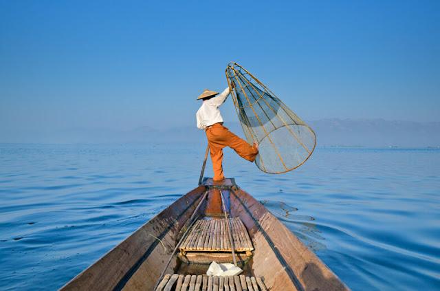 """Đến với Inle bạn chắc chắn sẽ ấn tượng với hình ảnh về kiểu đánh cá truyền thống đặc biệt của ngư dân trên hồ Inle: Chèo thuyền một chân, đứng ở cuối mũi thuyền, giữ thăng bằng và chụp lưới.    Để có được kỹ năng này, các ngư dân hồ Inle đã phải luyện kỹ thuật cân bằng, nhanh nhẹn và sức mạnh. Đây là một cách chèo thuyền đánh cá rất độc đáo dù ngày nay hầu như không còn ngư dân đánh cá theo cách này. Theo dòng xoáy du lịch, nhiều ngư dân đã bỏ nghề và chuyển qua tạo dáng """"làm xiếc"""" cho du khách chụp ảnh để kiếm tiền."""