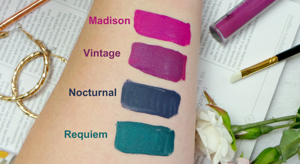 Image shows an arm with lipstick swatches. Top-Bottom, Madison a bright plum magenta, Vintage a deep orchid, nocturnal a dark blue and requiem a metallic teal.