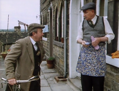 Howard from last of the summer wine cleaning windows with a pullover over his pinny, while Normal Clegg leans on his bike to talk to him