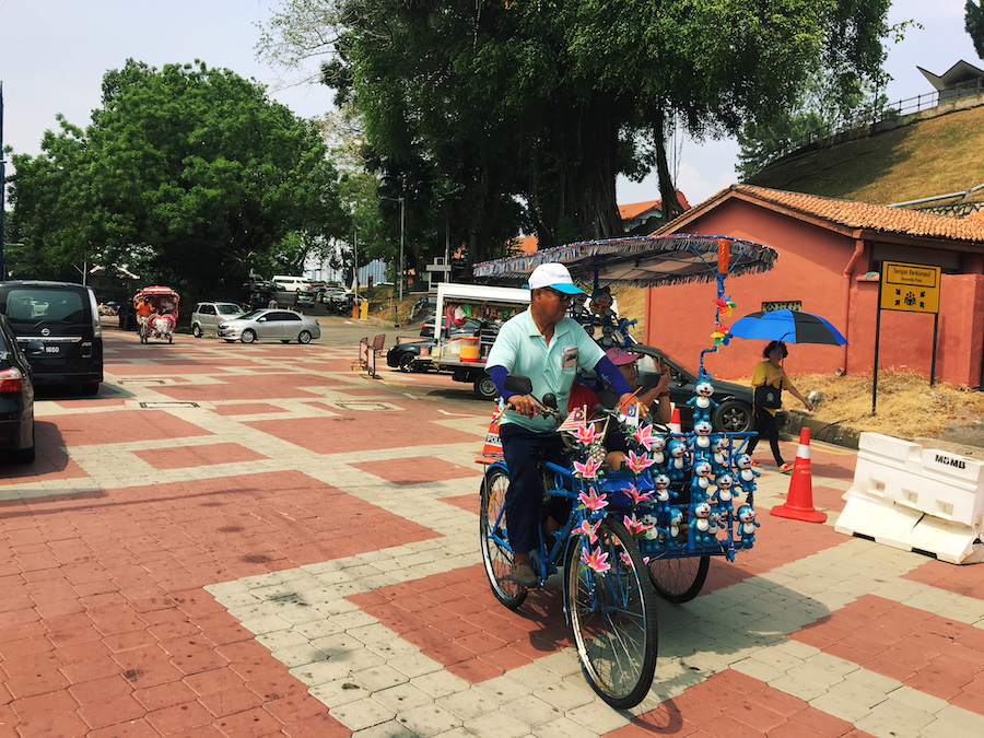 A hawker in Malacca with a flashy bike