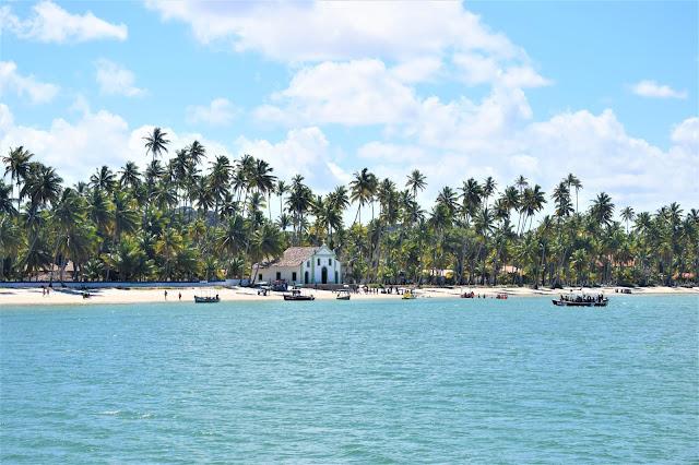 paisagem de praia com coqueiros e uma igreja