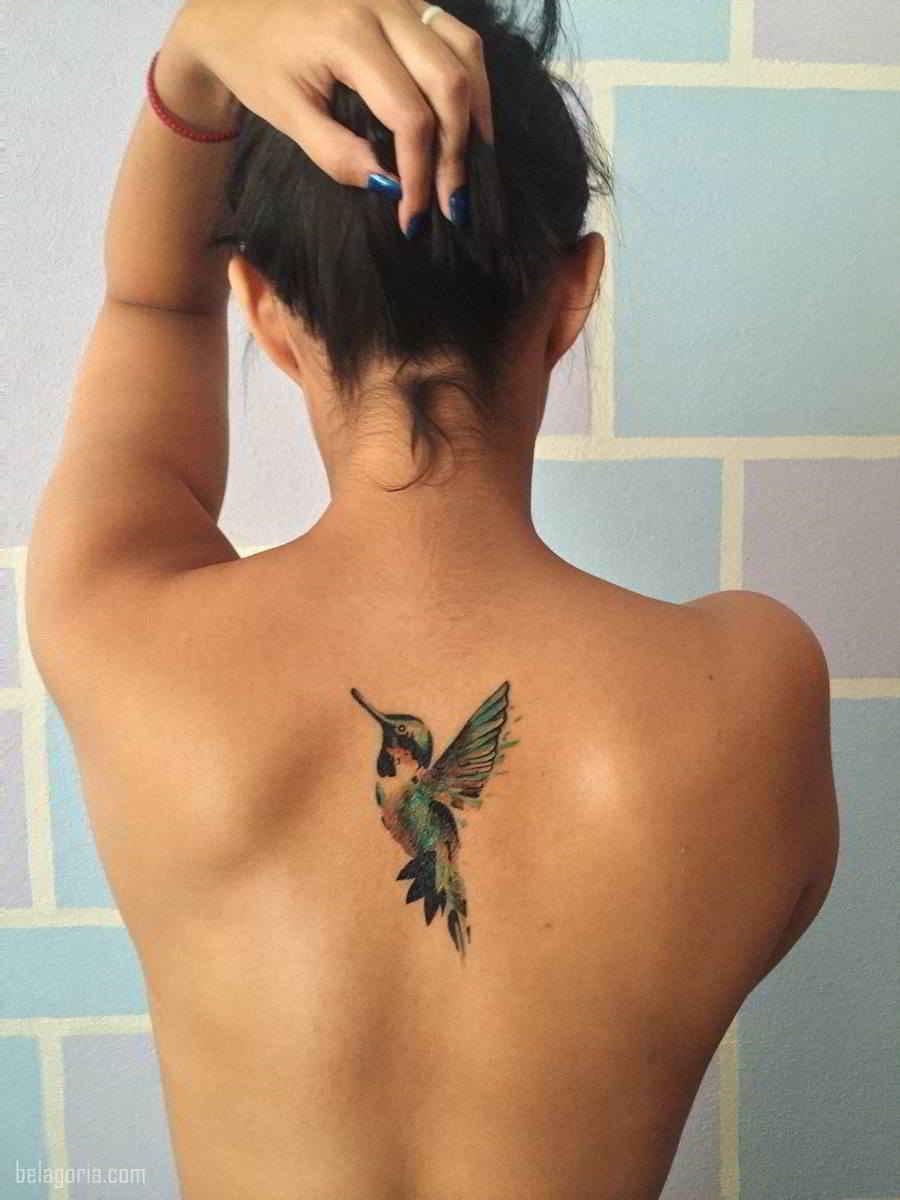 Foto de un tatuaje de colibri en la espalda de una mujer