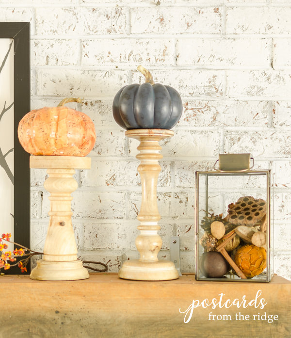 faux pumpkins on top of wooden candle holders