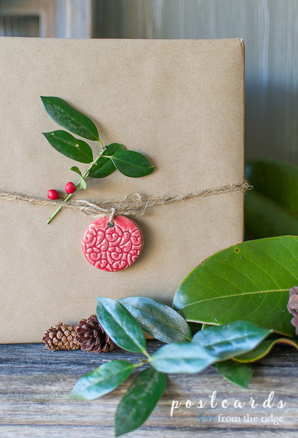 red clay ornament gift tag on package wrapped in brown kraft paper