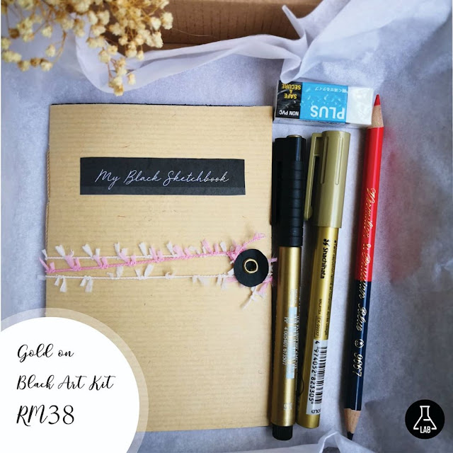 A box of stationery with gold markers