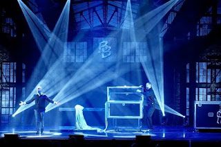 moody blue, black, and white lights shine on a stage with a box of black, clear, and silver, and magician Bill Blagg plus an assistant