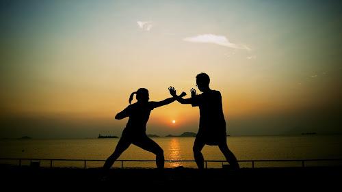 Um homem e uma mulher lutam kung fu ao por do sol