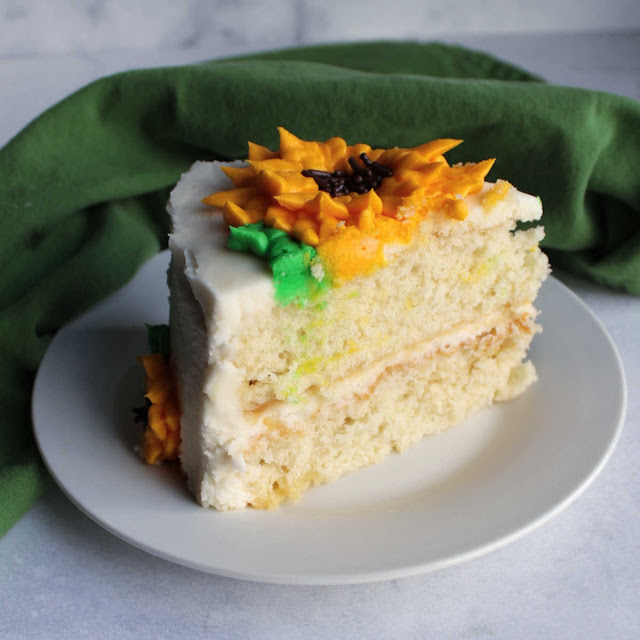 slice of layered white cake with white frosting and sunflower on top