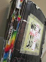 """One thing I finally finished up was cover and spine of my book. I had a problem with my book trying to """"shed its skin"""" so instead of letting the entire cover peel off, I went ahead and glued down the remaining pieces and colored the spine with crayons. I think it looks wicked now like a rainbow is trying to burst through the page seams or something."""