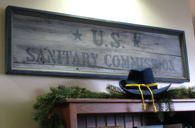 A framed piece of wood is used for a sign of the US sanitary commission