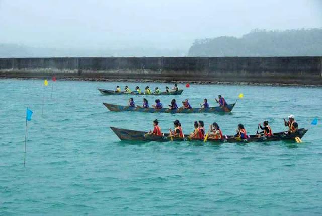 three wooden sabani boats, girls paddle in rain