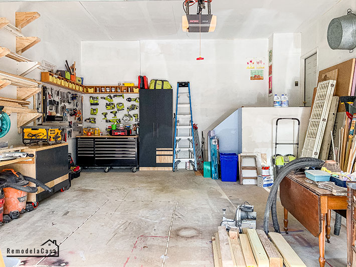 garage with mitersaw station, pegboard, tool storage bench