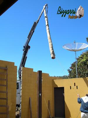 Caminhão munck ajeitando para chumbar os pilares de eucalipto tratado na construção da sala de estar com a suíte superior.