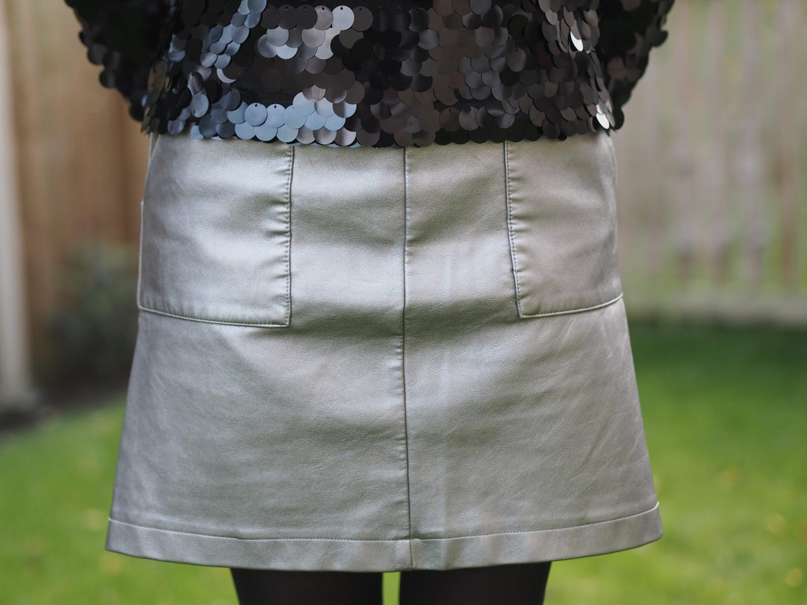 Black paillette sequin sweatshirt, metallic faux leather skirt, ankle boots, over 40