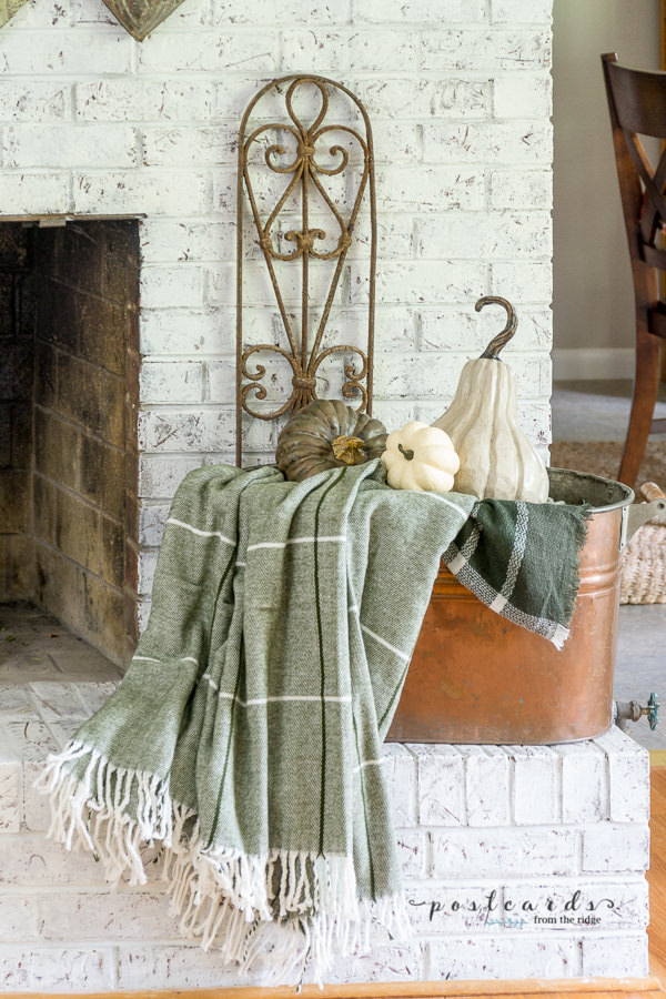 copper tub with green plaid blanket and scarf on a painted brick mantel