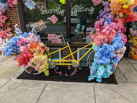 Tandem Bicycle with flowers in front of store