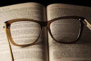 Imagem ilustrativa de um livro aberto sobre uma mesa com um óculos de grau aberto sobre este livro onde se pesquisa o artigo 4 da lei 12.112/09