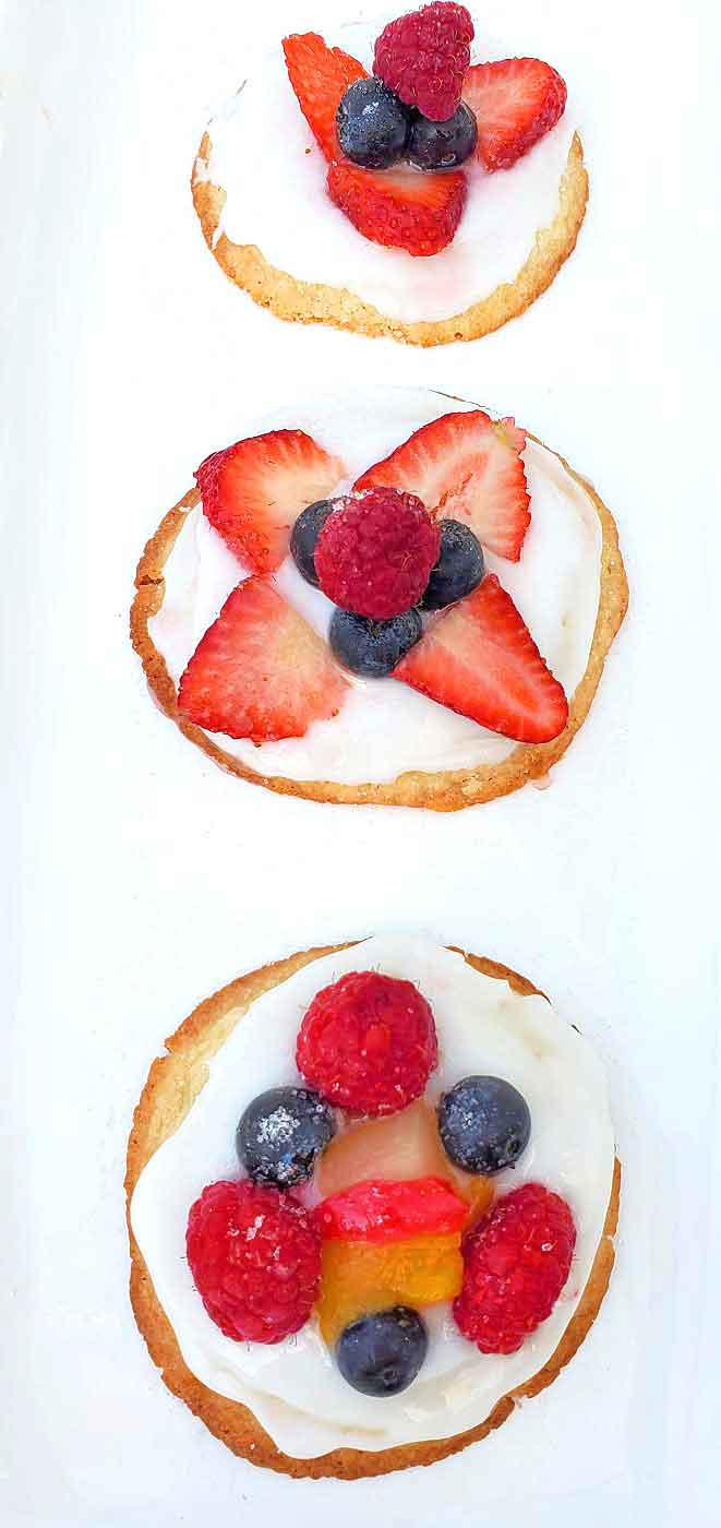 these are 3 mini fruit pizzas with marshmallow cream cheese frosting, berries and sugar cookies