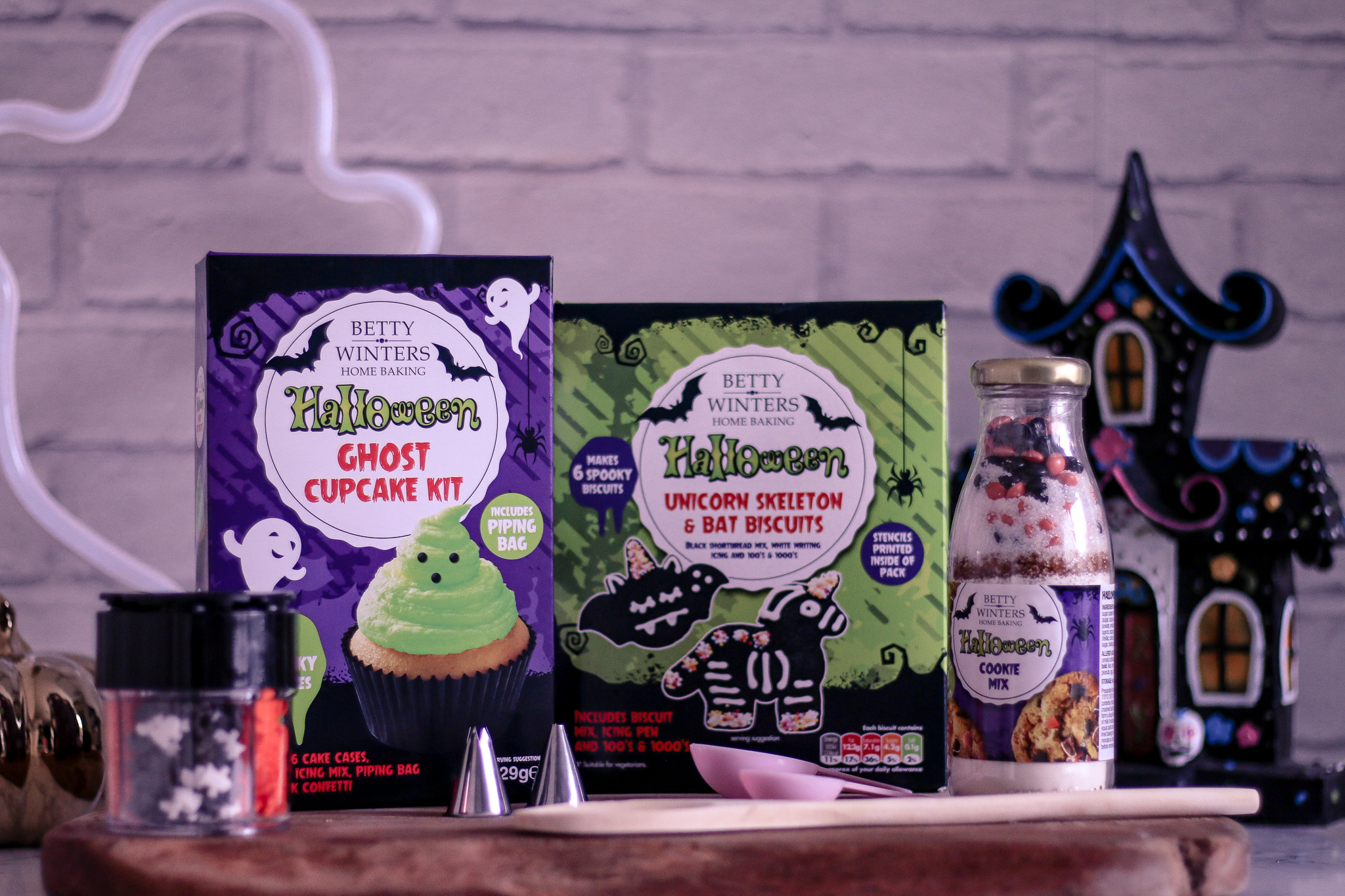 Photo of three betty winters home baking kits on top of a marble kitchen worktop with a ghost led light in the back left corner and a haunted house decoration in the back right corner