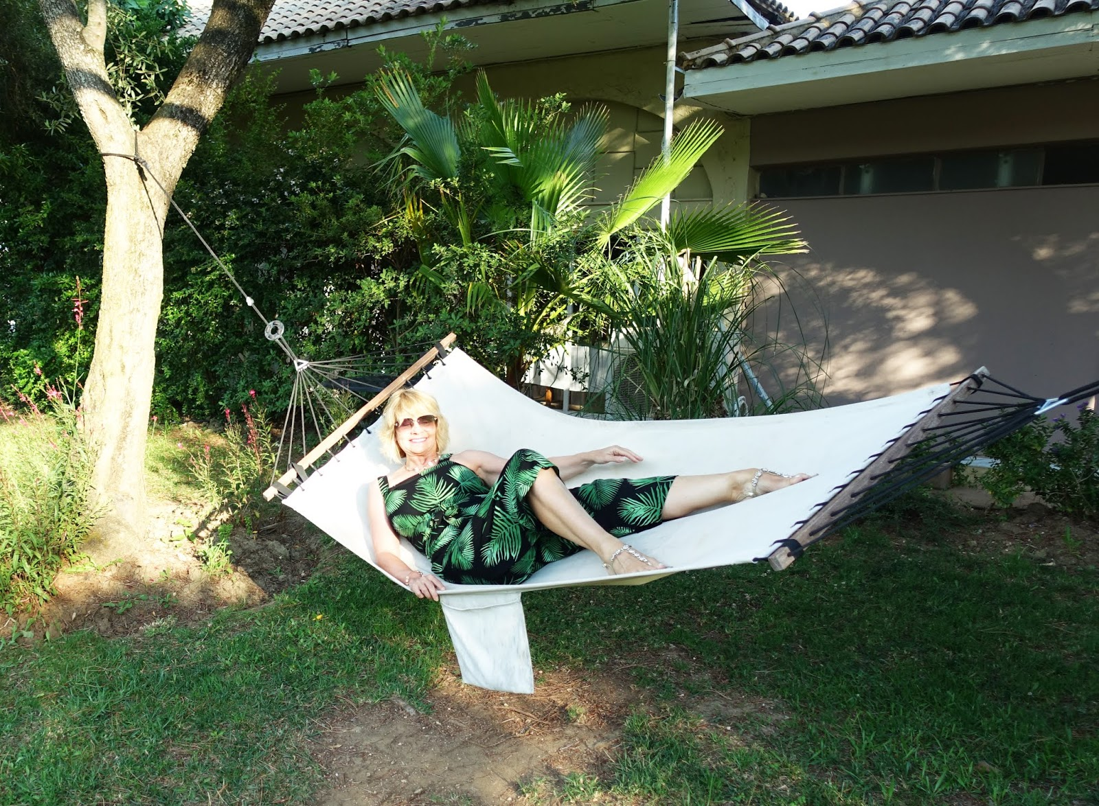 Is This Mutton blogger Gail Hanlon in palm patterned cropped jumpsuit on a hammock at the Parga Beach Resort