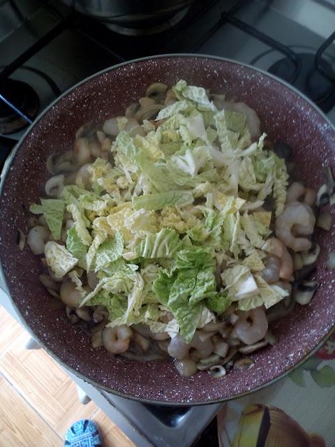 Ultimo paso del sofrito de cebolla, champiñones, gambas y col rizada
