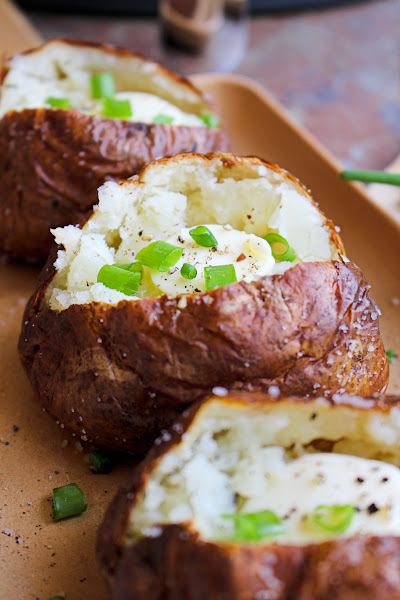 Side view of salty skin baked potatoes on a tan dish.