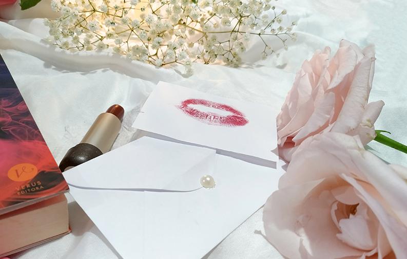 A imagem foca em um batom vermelho, aberto, e um bilhete ao lado com uma marca de boca. Ao lado desses objetos, e em primeiro plano, está um pequeno envelope branco, com uma pérola servindo de fecho.