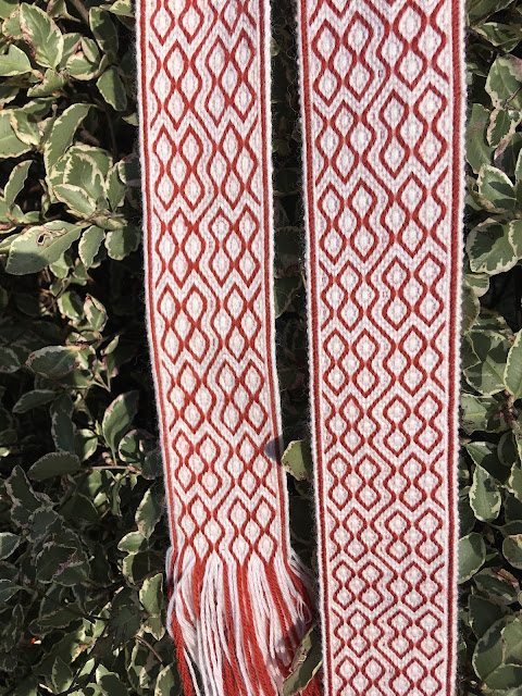 A white vacant-hole tablet woven band with red diamond and diagonal line motifs, photographed against a green leafy background