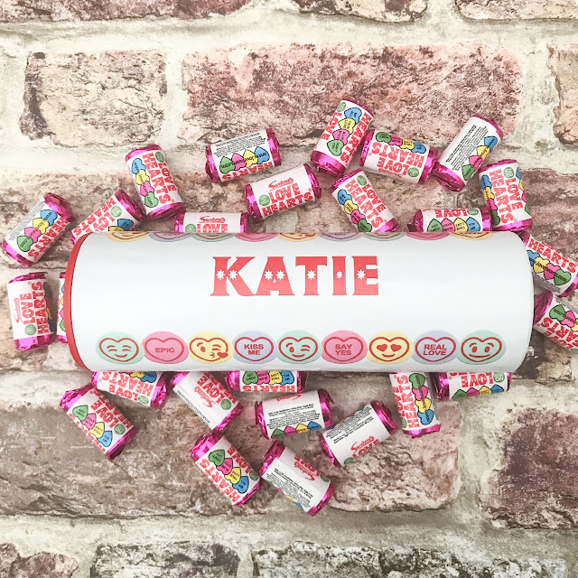 Tube designed to look like a large love heart tube with the name Katie across the centre, surrounded by small love heart sweets