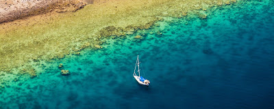 Vue aérienne, de la côte à Mayotte où un bateau à voile à jeté l'ancre.