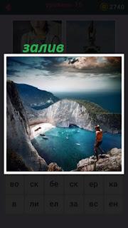 на горе стоит человек и смотрит на залив среди гор и пляж внутри