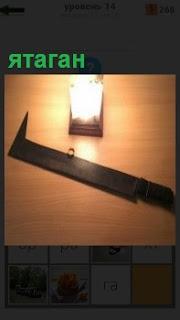 При свете бра на стене лежит меч ятаган, темного цвета в качестве холодного оружия