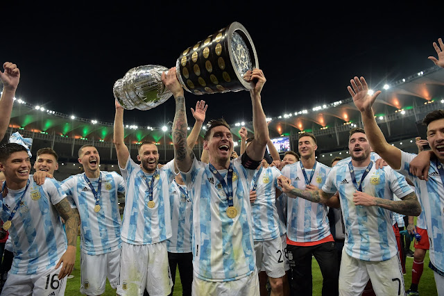 Lionel Messi and his Argentina teammate lifting the Copa America trophy