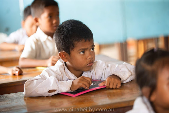 Young male Cambodian student listening intently for instructions as he holds his chalk and personal chalkboard