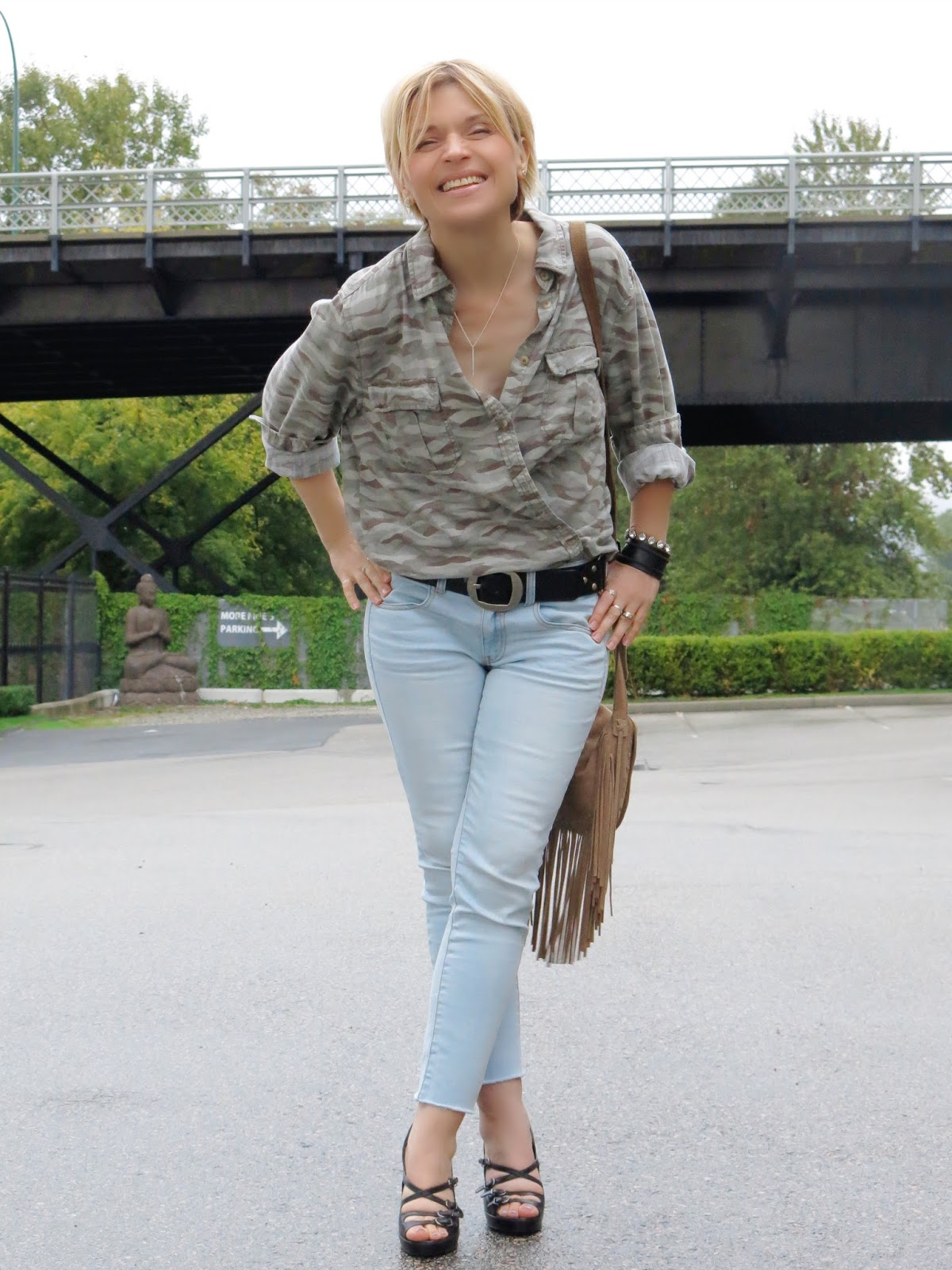 styling an oversized camo shirt with skinny jeans and strappy shoes